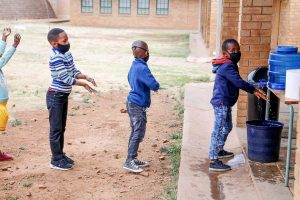 Kinder befolgen Covid-19 Hygienemaßnahmen